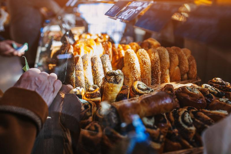 Ανώτερες πίτες αγοράς γυναικών στο κατάστημα Η συνταξιούχος γυναίκα κρατά τα χρήματα εκτός από την προθήκη με τα προϊόντα αρτοποι στοκ εικόνα με δικαίωμα ελεύθερης χρήσης
