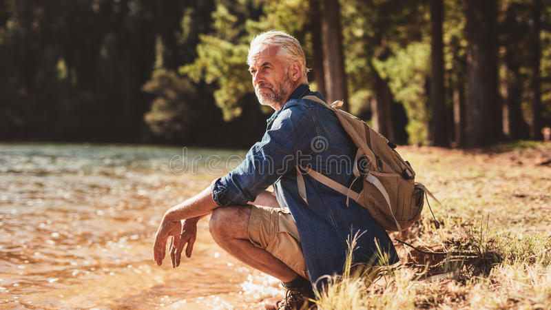 Ανώτερη αρσενική χαλάρωση οδοιπόρων από μια λίμνη και θαυμασμός της άποψης στοκ φωτογραφίες με δικαίωμα ελεύθερης χρήσης