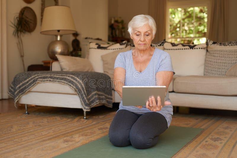Ανώτερη γιόγκα άσκησης γυναικών με μια ψηφιακή ταμπλέτα στο σπίτι στοκ φωτογραφίες
