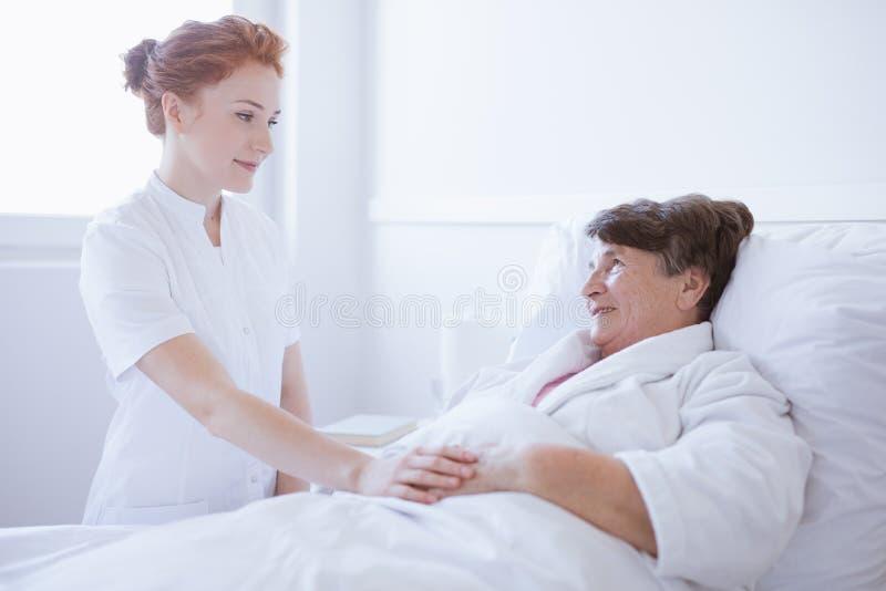 Ανώτερη γκρίζα γυναίκα που βρίσκεται στο άσπρο νοσοκομειακό κρεβάτι με τη νέα χρήσιμη νοσοκόμα που κρατά το χέρι της στοκ φωτογραφία