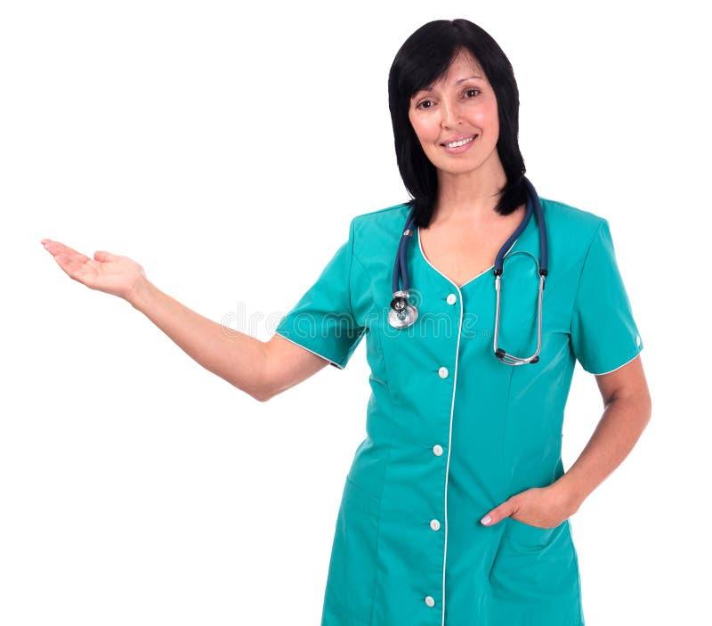 Ανώτερη γυναίκα ή νοσοκόμα γιατρών κάτι, που απομονώνεται που παρουσιάζει στο W στοκ εικόνα με δικαίωμα ελεύθερης χρήσης