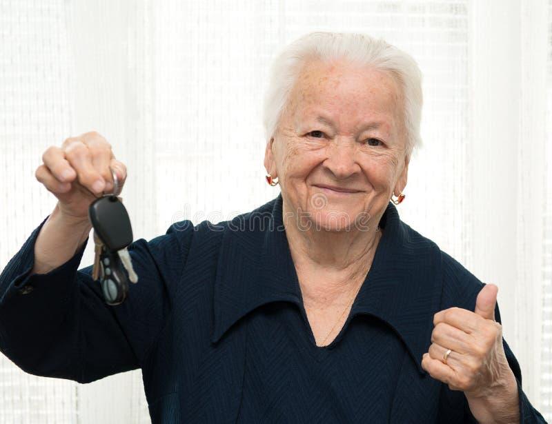 Ανώτερη γυναίκα με ένα κλειδί και την κατασκευή αυτοκινήτων της ΕΝΤΑΞΕΙ χειρονομίας στοκ εικόνα