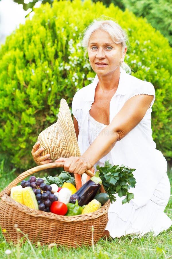 Ανώτερη γυναίκα με ένα σύνολο καλαθιών των συγκομισμένων φρούτων και λαχανικών στοκ φωτογραφία με δικαίωμα ελεύθερης χρήσης