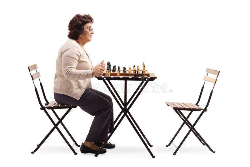 Ανώτερη γυναίκα με μια σκακιέρα σε έναν πίνακα που εξετάζει μια κενή καρέκλα στοκ φωτογραφία με δικαίωμα ελεύθερης χρήσης