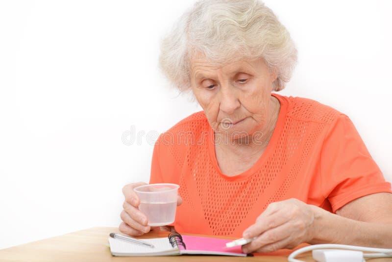 Ανώτερη γυναίκα με τα χάπια και το ποτήρι του νερού στο σπίτι στοκ εικόνες