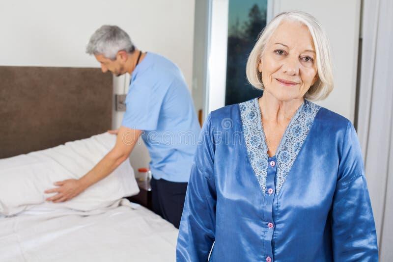 Ανώτερη γυναίκα με τον επιστάτη που κάνει το κρεβάτι στην περιποίηση στοκ εικόνες