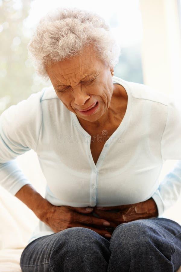 Ανώτερη γυναίκα με τον πόνο στομαχιών στοκ εικόνες