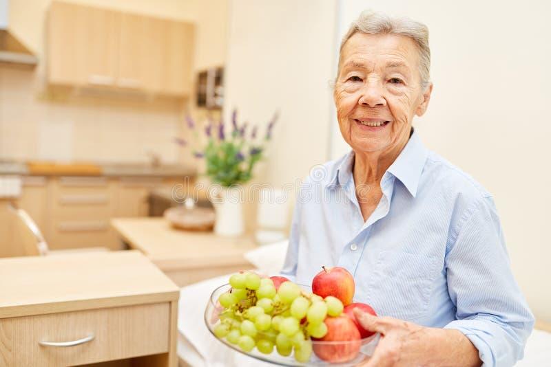 Ανώτερη γυναίκα με το μήλο και τα σταφύλια στοκ φωτογραφίες