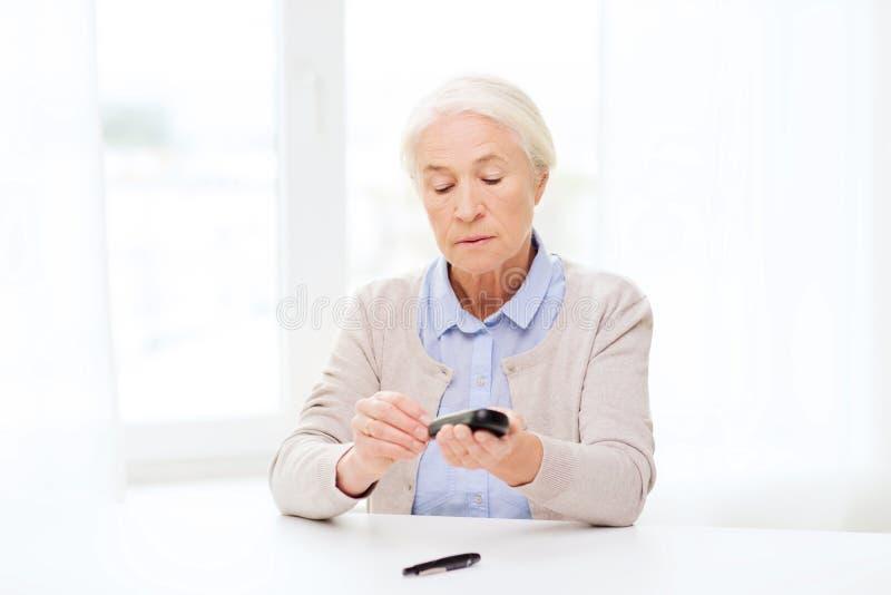 Ανώτερη γυναίκα με το glucometer που ελέγχει τη ζάχαρη αίματος στοκ εικόνες