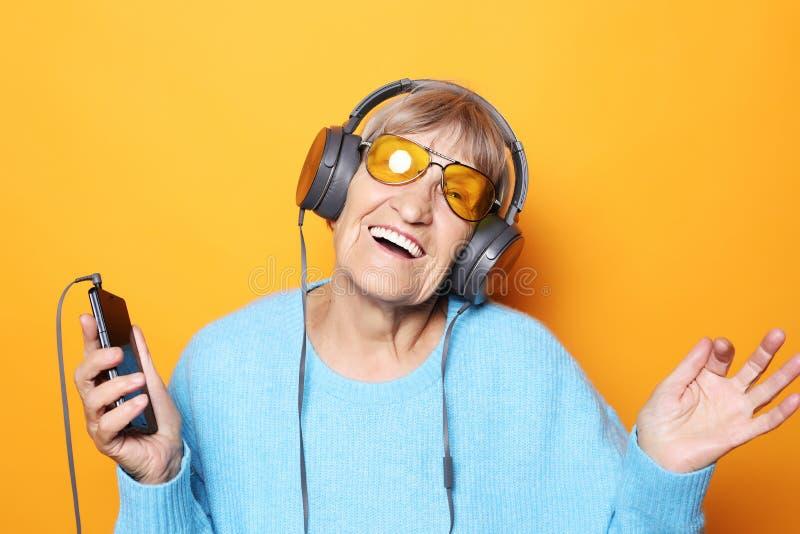 Ανώτερη γυναίκα που ακούει τη μουσική με το smartphone στοκ εικόνα με δικαίωμα ελεύθερης χρήσης