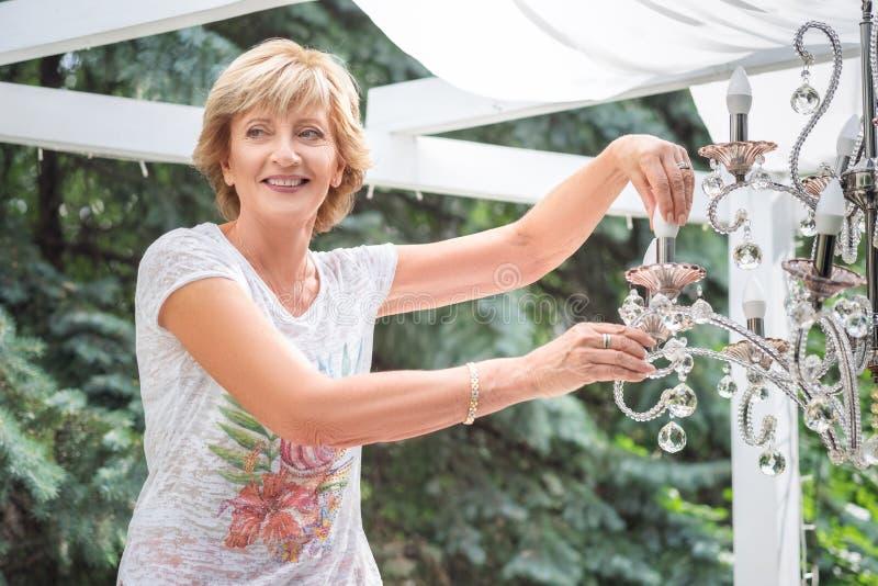 Ανώτερη γυναίκα που αλλάζει μια λάμπα φωτός σε έναν πολυέλαιο στοκ εικόνα