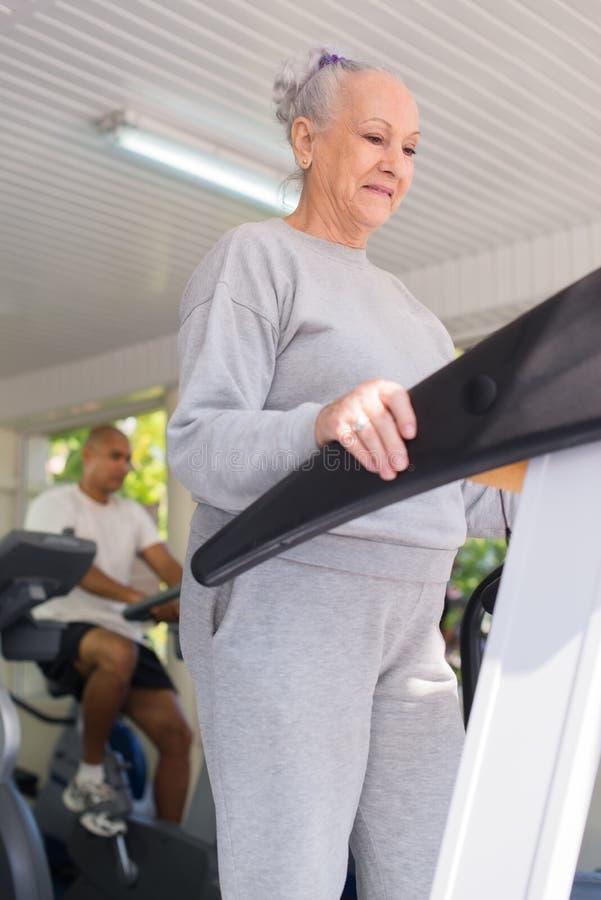 Ανώτερη γυναίκα που ασκεί στη λέσχη wellness στοκ εικόνες