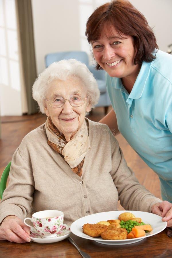 Ανώτερη γυναίκα που είναι εξυπηρετούμενο γεύμα από το φροντιστή στοκ φωτογραφία με δικαίωμα ελεύθερης χρήσης
