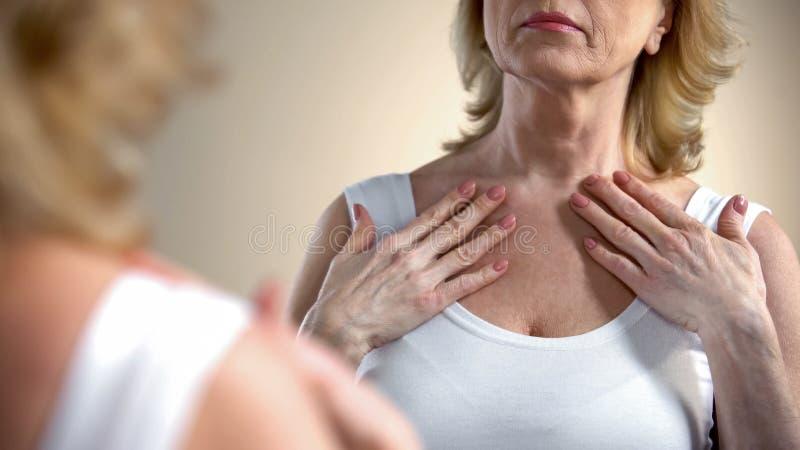 Ανώτερη γυναίκα που εξετάζει την αντανάκλαση καθρεφτών, συνέπειες διαδικασίας γήρανσης, προσοχή σωμάτων στοκ εικόνες