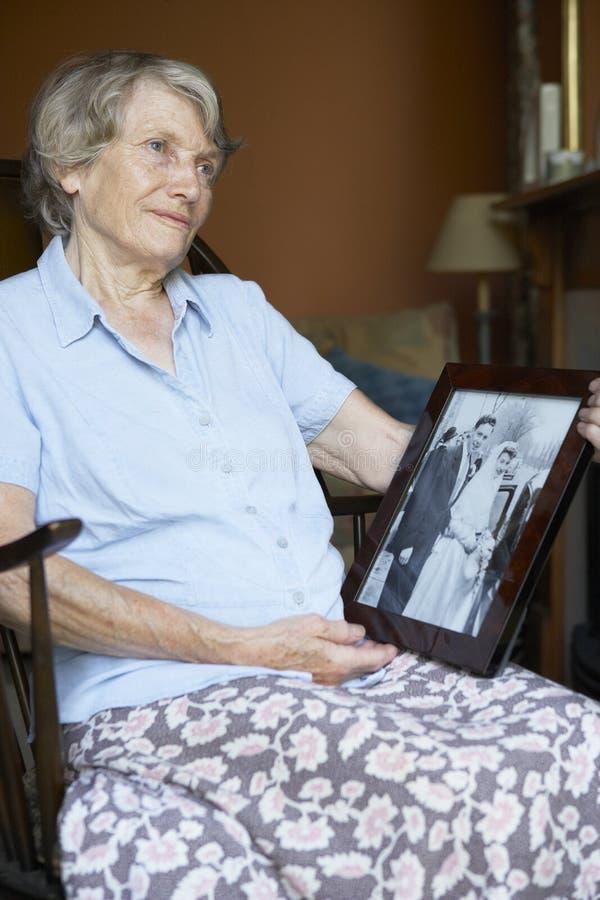 Ανώτερη γυναίκα που εξετάζει την παλαιά γαμήλια φωτογραφία στοκ εικόνες
