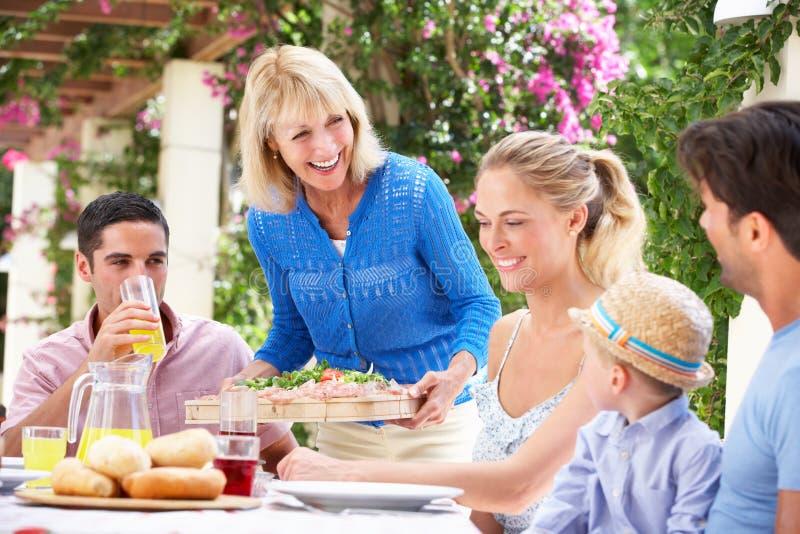 Ανώτερη γυναίκα που εξυπηρετεί ένα οικογενειακό γεύμα έξω στοκ φωτογραφίες