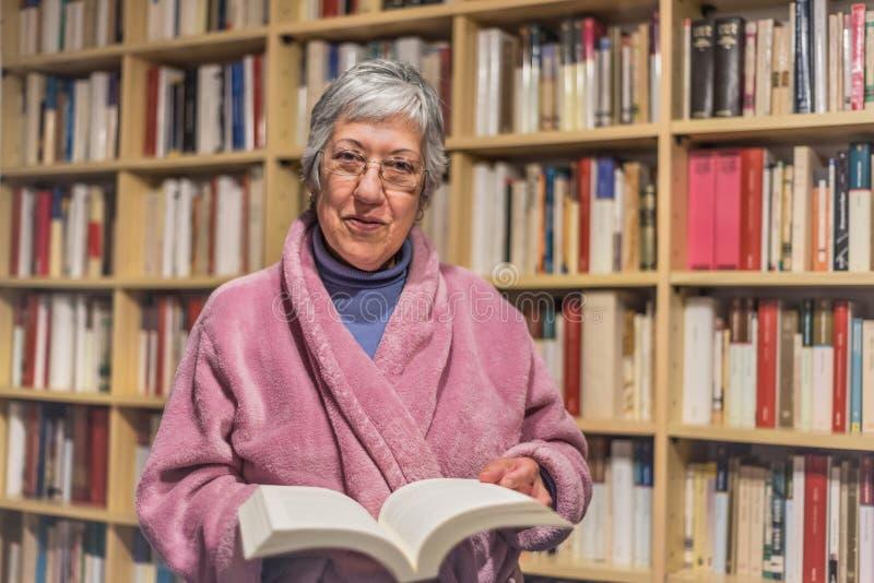 Ανώτερη γυναίκα που διαβάζει ένα βιβλίο στο σπίτι έκφραση ευτυχής Θολωμένο στοκ εικόνα με δικαίωμα ελεύθερης χρήσης