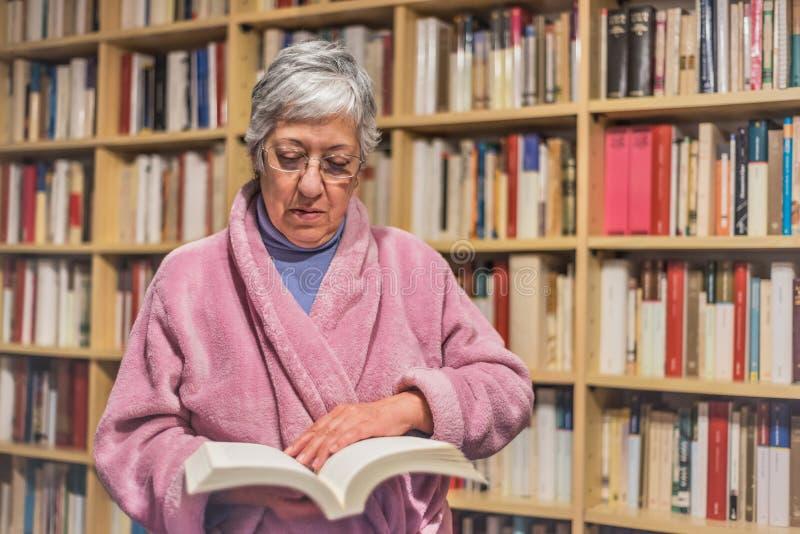 Ανώτερη γυναίκα που διαβάζει ένα βιβλίο στο σπίτι συγκεντρωμένη έκφραση Α στοκ εικόνες