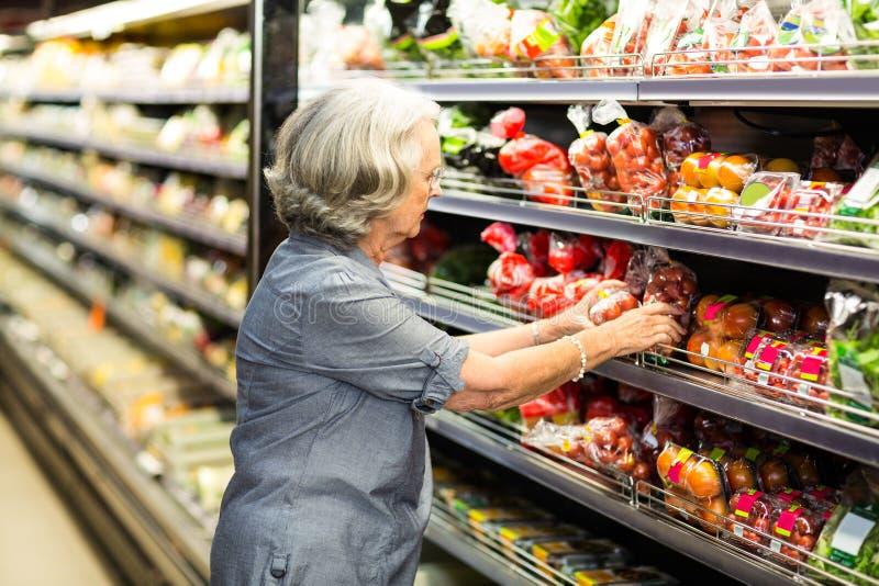 Ανώτερη γυναίκα που διαλέγει μερικά λαχανικά στοκ εικόνες