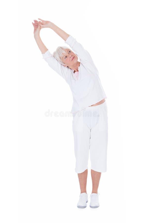 Ανώτερη γυναίκα που κάνει την τεντώνοντας άσκηση πέρα από το άσπρο υπόβαθρο στοκ εικόνες με δικαίωμα ελεύθερης χρήσης