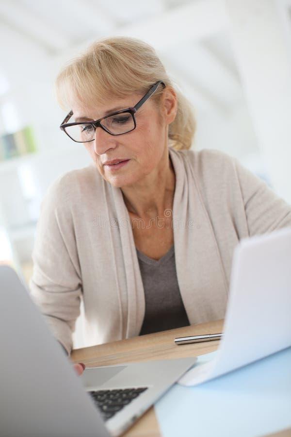 Ανώτερη γυναίκα που κάνει τη γραφική εργασία διοίκησης στοκ φωτογραφία
