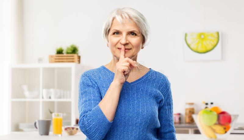 Ανώτερη γυναίκα που κάνει shush τη χειρονομία στην κουζίνα στοκ φωτογραφία με δικαίωμα ελεύθερης χρήσης