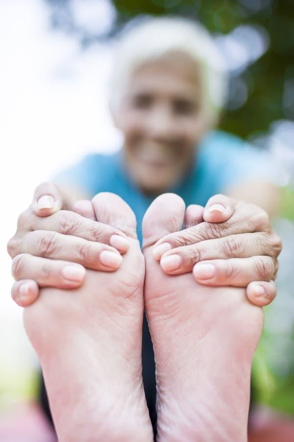 Ανώτερη γυναίκα που κάνουν τη γιόγκα και πόδια που τεντώνουν στο πάρκο στοκ φωτογραφία με δικαίωμα ελεύθερης χρήσης