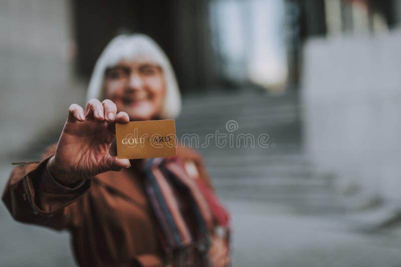 Ανώτερη γυναίκα που καταδεικνύει τη χρυσή κάρτα στο θολωμένο υπόβαθρο στοκ εικόνες με δικαίωμα ελεύθερης χρήσης