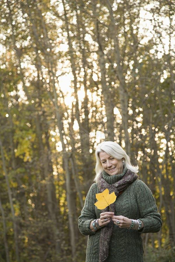 Ανώτερη γυναίκα που κρατά ένα φύλλο στοκ εικόνες με δικαίωμα ελεύθερης χρήσης
