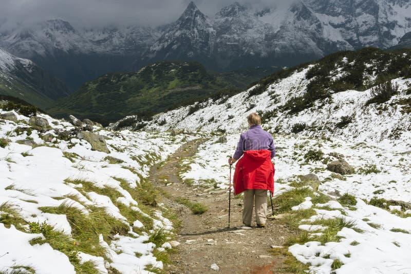 Ανώτερη γυναίκα που μέσω των χιονωδών βουνών, Αυστρία στοκ εικόνα