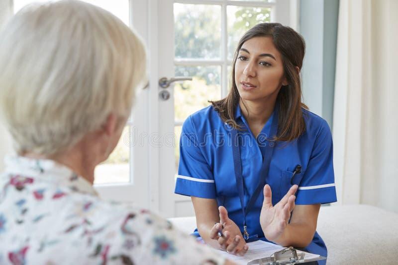 Ανώτερη γυναίκα που μιλά στη νέα νοσοκόμα προσοχής στην εγχώρια επίσκεψη στοκ εικόνες