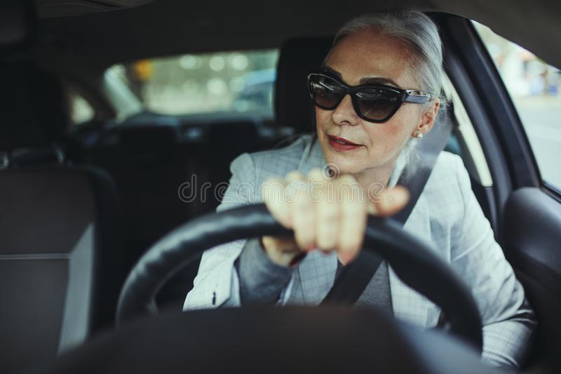 Ανώτερη γυναίκα που οδηγεί ένα σύγχρονο αυτοκίνητο στοκ εικόνες