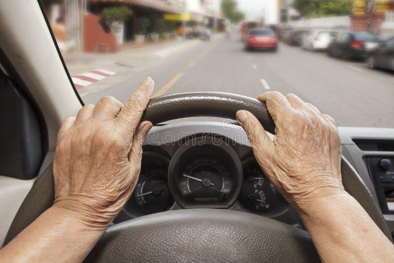 Ανώτερη γυναίκα που οδηγεί ένα αυτοκίνητο στην οδό στοκ εικόνες