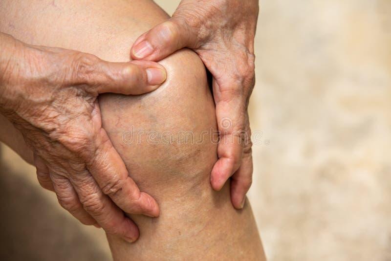 Ανώτερη γυναίκα που πάσχει από τη συνεδρίαση πόνου γονάτων στην καρέκλα, που τρίβει από το χέρι της, έννοια σώματος στοκ εικόνες με δικαίωμα ελεύθερης χρήσης