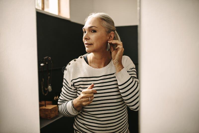 Ανώτερη γυναίκα που προσπαθεί σε ένα δαχτυλίδι αυτιών στο κατάστημα κοσμήματος στοκ εικόνα