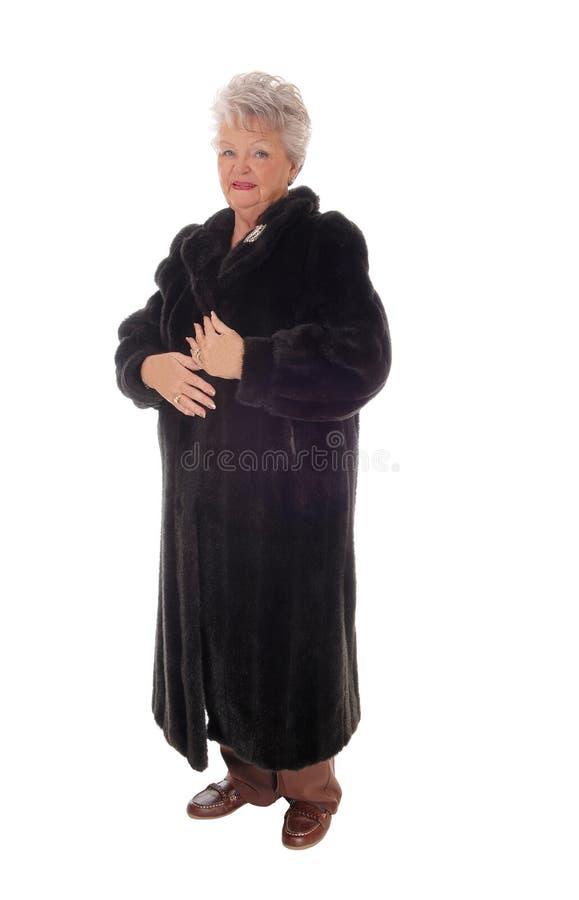 Ανώτερη γυναίκα που στέκεται στο παλτό γουνών στοκ εικόνα με δικαίωμα ελεύθερης χρήσης