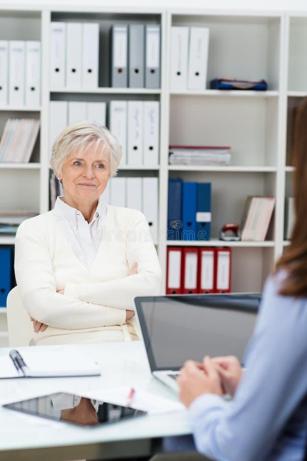 Ανώτερη γυναίκα που συμμετέχει σε μια συνεδρίαση σε ένα γραφείο στοκ εικόνες