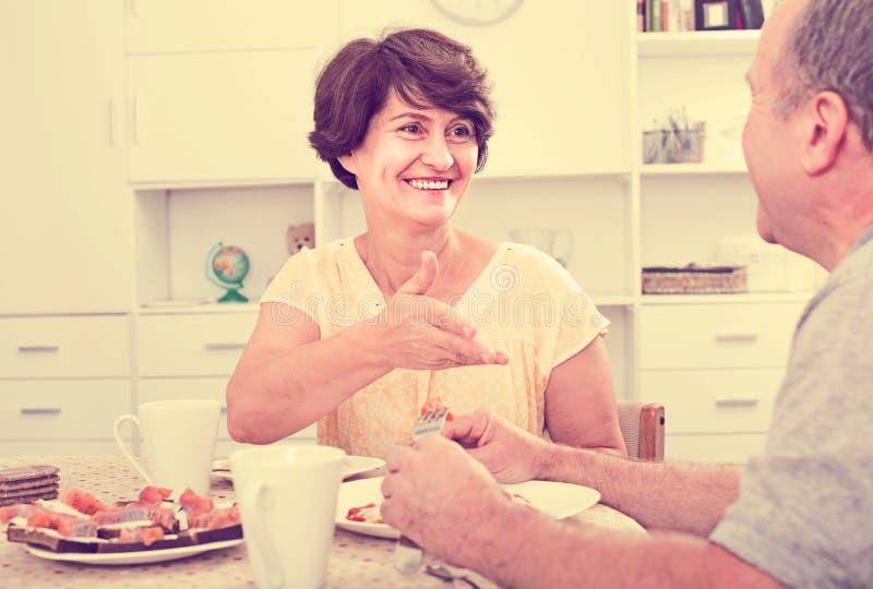 Ανώτερη γυναίκα που τρώει με τον άνδρα στο σπίτι στοκ φωτογραφία με δικαίωμα ελεύθερης χρήσης