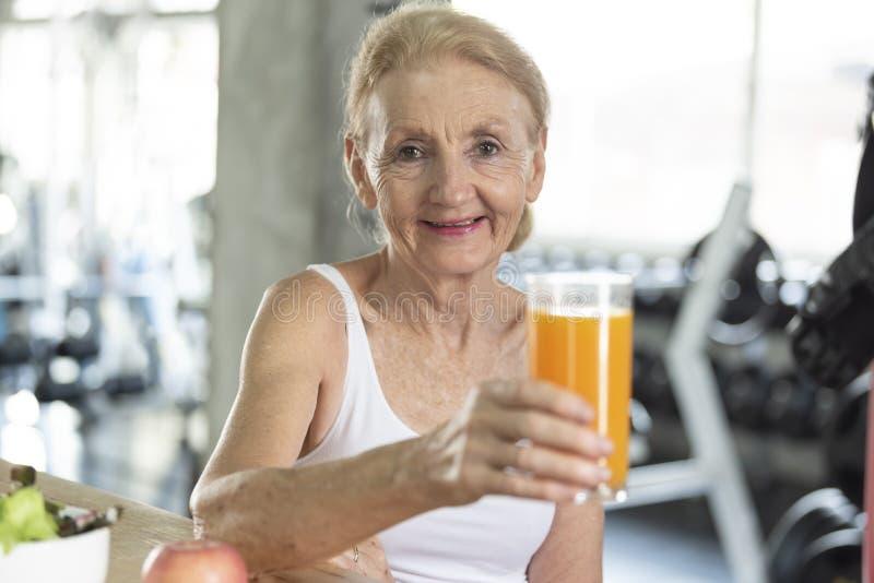 Ανώτερη γυναίκα που τρώει την υγιή σαλάτα και το χυμό από πορτοκάλι ηλικιωμένη έννοια διατροφής τρόπου ζωής υγείας στοκ φωτογραφία με δικαίωμα ελεύθερης χρήσης