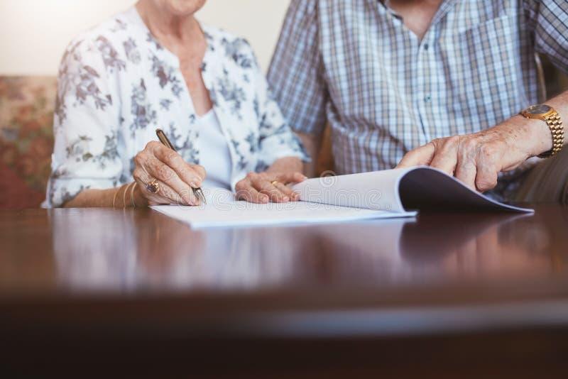 Ανώτερη γυναίκα που υπογράφει τα έγγραφα με το σύζυγό της στοκ εικόνες