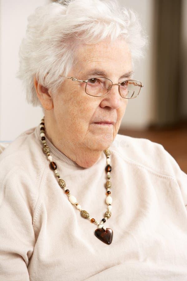 Ανώτερη γυναίκα που φαίνεται λυπημένη στην έδρα στοκ φωτογραφίες με δικαίωμα ελεύθερης χρήσης