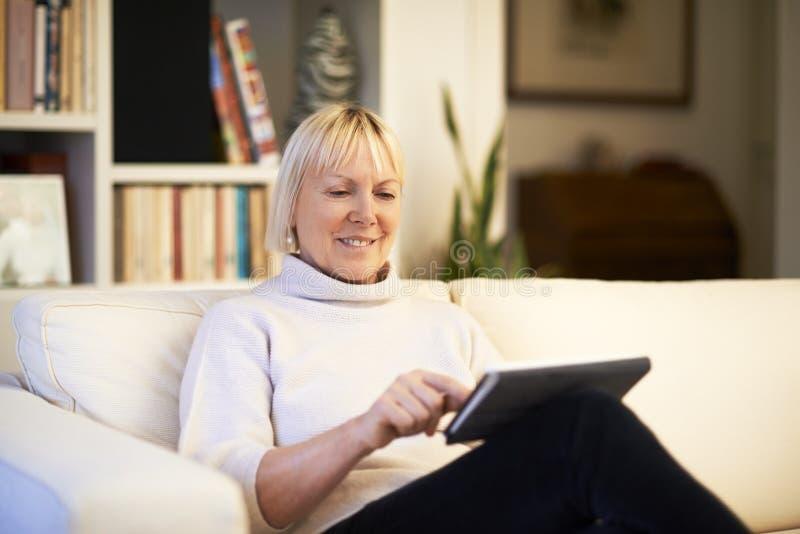Ανώτερη γυναίκα που χρησιμοποιεί τη συσκευή μαξιλαριών αφής στοκ φωτογραφίες με δικαίωμα ελεύθερης χρήσης