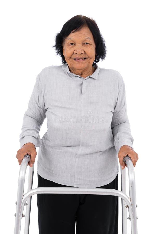 Ανώτερη γυναίκα που χρησιμοποιεί τον περιπατητή που απομονώνεται στο άσπρο υπόβαθρο στοκ φωτογραφία με δικαίωμα ελεύθερης χρήσης