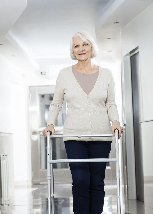 Ανώτερη γυναίκα που χρησιμοποιεί τον περιπατητή στο κέντρο Rehab στοκ εικόνα με δικαίωμα ελεύθερης χρήσης