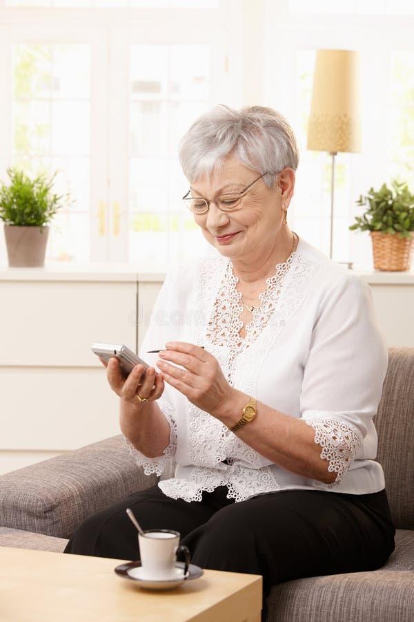 Ανώτερη γυναίκα που χρησιμοποιεί palmtop στοκ φωτογραφία