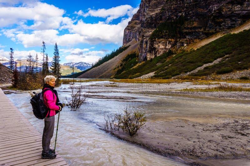 Ανώτερη γυναίκα σε ένα πεζοπορώ στο Lake Louise στα δύσκολα βουνά στοκ φωτογραφία με δικαίωμα ελεύθερης χρήσης