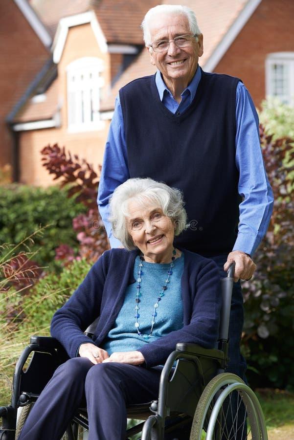 Ανώτερη γυναίκα στην αναπηρική καρέκλα που ωθείται από το σύζυγο στοκ φωτογραφίες με δικαίωμα ελεύθερης χρήσης
