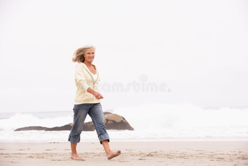Ανώτερη γυναίκα στις διακοπές που τρέχουν κατά μήκος της παραλίας στοκ φωτογραφίες