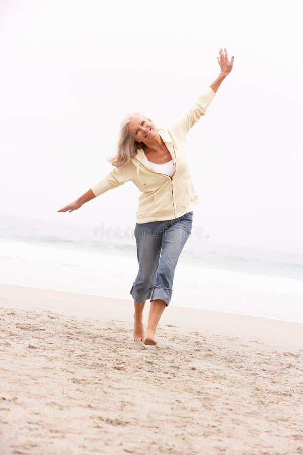 Ανώτερη γυναίκα στις διακοπές που τρέχουν κατά μήκος της χειμερινής παραλίας στοκ εικόνες