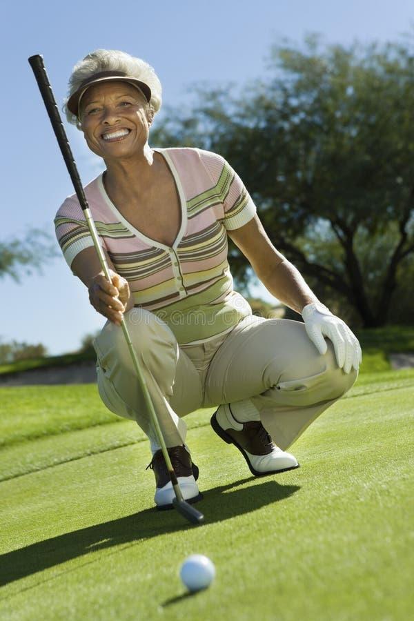 Ανώτερη γυναίκα στο γήπεδο του γκολφ στοκ φωτογραφίες